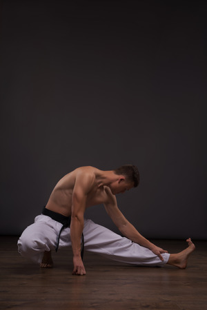 barechested: Full-length portrait of young handsome fair-haired bare-chested karate enthusiast stretching. Isolated on the dark background Stock Photo