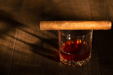 distilled alcohol: Selective focus on the Cuban cigar lying on the glass of whiskey that standing on the wooden table Stock Photo