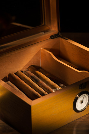 hygrometer: Selective focus on the great vintage humidor with Cuban cigars