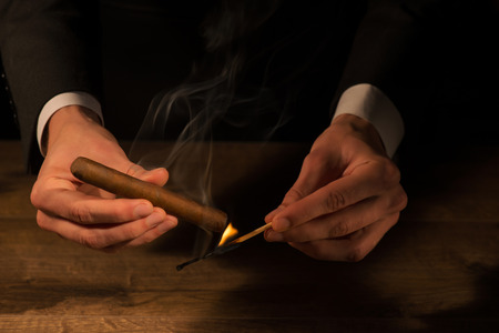 Selective focus on the hands of the man lighting up the cigar with help of matches photo
