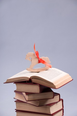 Little wooden toy horse standing on the heap of different books. Isolated on the grey background photo