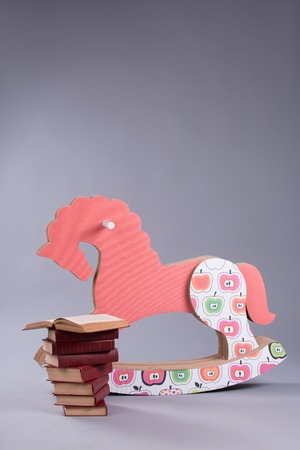 Wooden toy funny horse standing near the heap of books. Isolated on the grey background photo