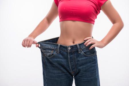 Nahaufnahme der schlanke Taille der jungen Frau in den großen Jeans zeigt eine erfolgreiche Gewichtsabnahme, isoliert auf weißem Hintergrund, Diät-Konzept