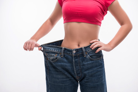 Close-up of slim waist of young woman in big jeans showing successful weight loss, isolated on white background, diet concept Foto de archivo