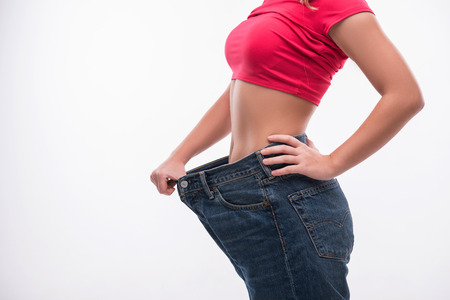 fat and slim: Close-up side view portrait of slim waist of young woman in big jeans showing successful weight loss, isolated on white background