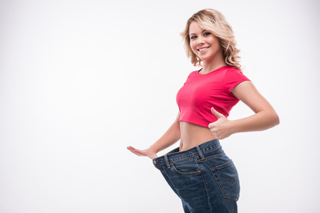 Full-length portrait of attractive slim young smiling woman in big jeans showing successful weight loss with her thumb up, isolated on white background