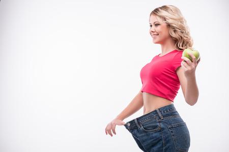 白い背景に分離成功した減量を示すリンゴを保持大きなジーンズで魅力的なスリムな若い笑顔の女性の全身肖像画 写真素材