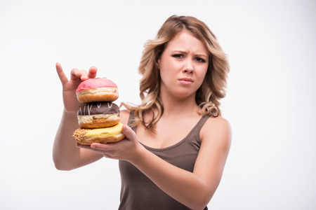 Half-length portrait of young attractive woman rejecting doughnuts isolated on white background, selected focus, diet concept