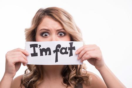 gordo: Primer retrato de la joven rubia atractiva con horror con tarjeta diciendo que ella es la grasa, el concepto de dieta, aislados en blanco