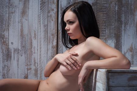 sauna nackt: Portrait von sexy junge nackte Brünette beiseite sitzen in der Sauna legte ihre Hand auf die Brust Blick auf etwas setzen, um ihre Gedanken