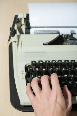 Working at the typewriter. Close-up of man typing something\ on typewriter
