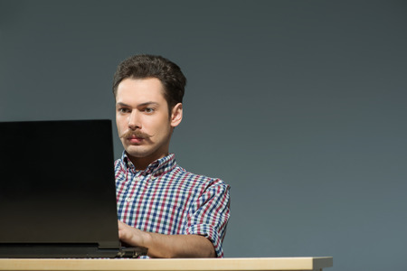 surfing the net: Surfing the net. Close-up of hipster with moustache using laptop while sitting against grey background Stock Photo