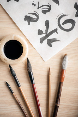 Compositions of brushes for calligraphy lesson. Closeup image of beautifully arranged brushes for oriental writing with ink bottle on wooden table photo