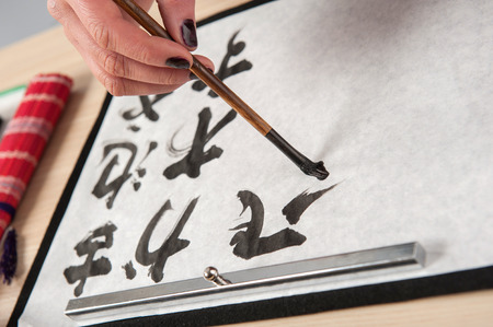 hieroglyph: Writing hieroglyph. Top view image of woman hand practicing calligraphy with brush on paper placed on wooden table