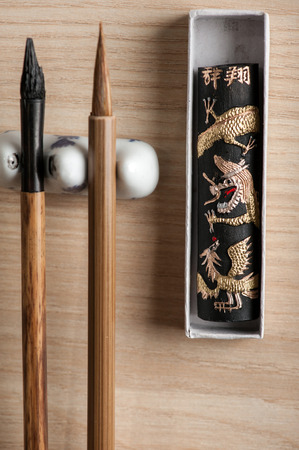Sophisticated art of calligraphy. Closeup image of brushes and other tools for Japanese or Chinese calligraphy accurately prepared on wooden table photo