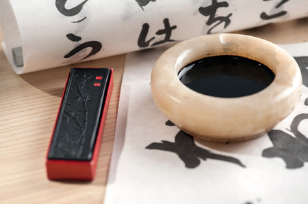 Mysterious Chinese writing. Closeup image of brushes, inkbottle and folded paper with hieroglyphs arranged on wooden table photo