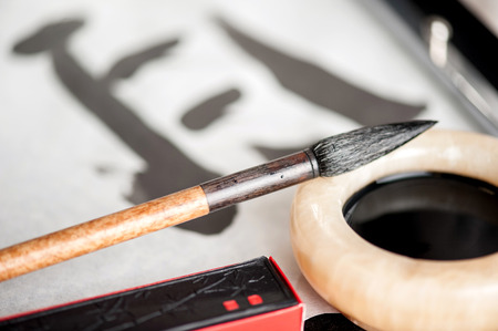 Beautiful art of calligraphy. Closeup image of working process of painting hieroglyphs with ink bottle and brushed on wooden table photo