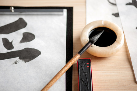 Beautiful art of calligraphy. Closeup image of working process of painting hieroglyphs with ink bottle and brushed on wooden table