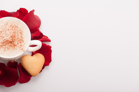 recipe decorated: Fresh coffee with love. Top view image of lovely heart shape cookie and an exquisite cup of cappuccino arranged with copy space on white background and decorated with rose petals