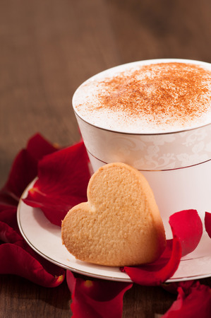 recipe decorated: Lovely moment. Closeup image of heart shape cookie and cup of coffee placed with copy space on wooden table and decorated with rose petals