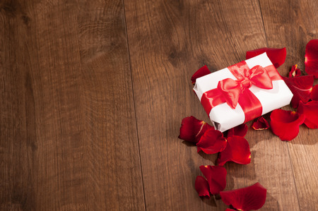 Gift to Saint Valentines Day. Top view image of white present box with red ribbon on top decorated with rose petals on wooden background with copy space photo