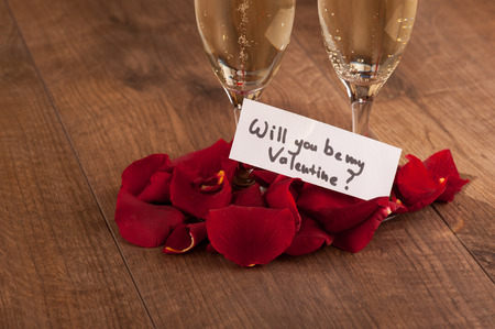 saint valentine's day: Let us celebrate. Closeup image of champagne glasses decorated with rose petals and greeting card devoted to Saint Valentines Day celebration arranged on wooden background Stock Photo