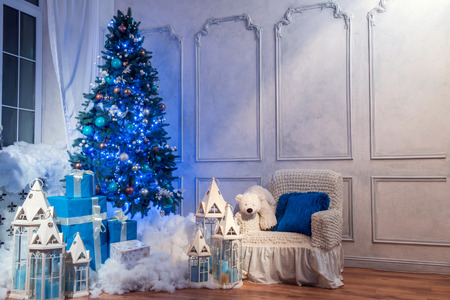 beautifully wrapped: Christmas interior. Beautifully decorated Christmas interior with high blue fur tree surrounded by white lanterns, candles and wrapped presents covered with decorative snow Stock Photo