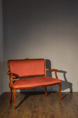 red couch: Vintage. Classic red elegant couch standing against grey wall