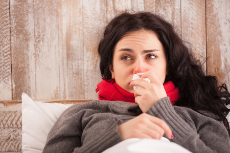 Sick woman caught a cold. Closeup image of frustrated young woman with red nose lying in bed with thick scarf and sneezing into tissue Reklamní fotografie