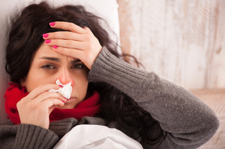 Flu. Closeup image of frustrated sick woman with red nose lying in bed in thick scarf holding tissue by her nose and touching her head
