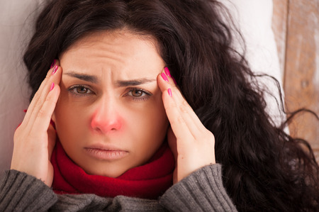 Flu or cold. Closeup top view image of frustrated young woman with red nose and suffering from terrible headache while lying in bed