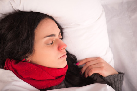 sniffle: Feeling unwell. Closeup image of young sick woman sleeping in bed with sore throat in scarf Stock Photo