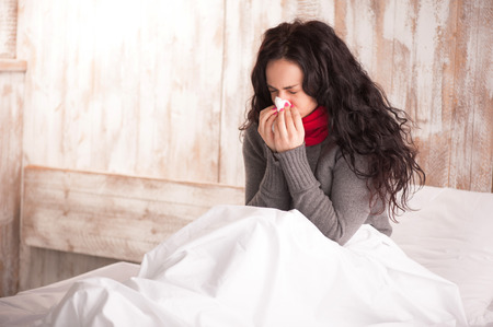 Blowing her nose. Young beauty with scarf on her neck sitting in bed with tissue and sneezing in her country house