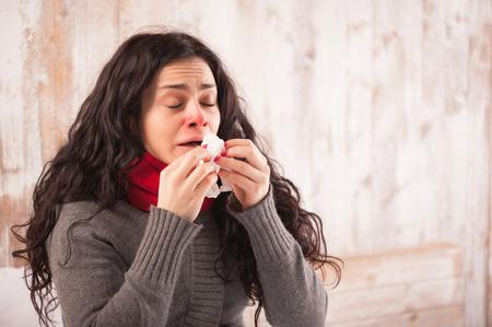 Tüsszögés szépség. Fiatal beteg nő sállal a nyakán ül az ágyban, és tüsszögés vele tájház a háttérben
