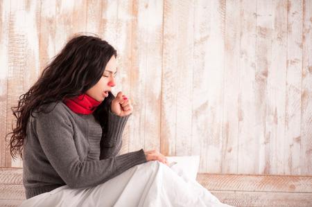 tosiendo: Tos belleza. Side imagen vista de joven mujer enferma con la bufanda en el cuello sentado en la cama y tos con su casa de campo en el fondo