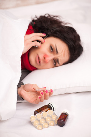 sick leave: On sick leave. Young sick woman in thick scarf talking over the telephone and holding thermometer while lying in bed and having medicines and lozenges on the blanket Stock Photo
