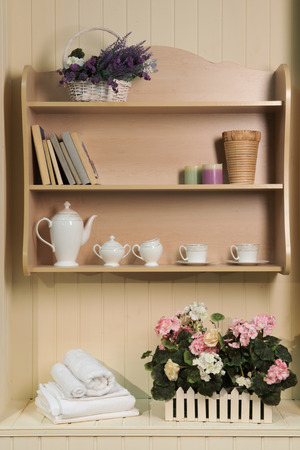 provencal: Fragment of interior design in Provence style  decorated with shelves and books, elegant tea set and Provencal flowers