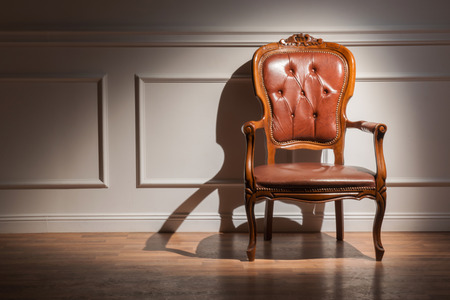 molding: Classic interior. Interior design with elegant brown classic armchair standing in light against white wall decorated with moldings