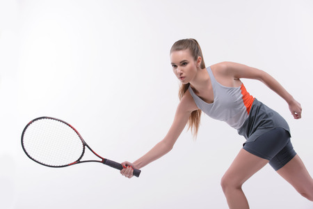 tennis racket: I am in game. Beautiful young woman in sports clothes holding tennis racket and looking  away while standing against white background