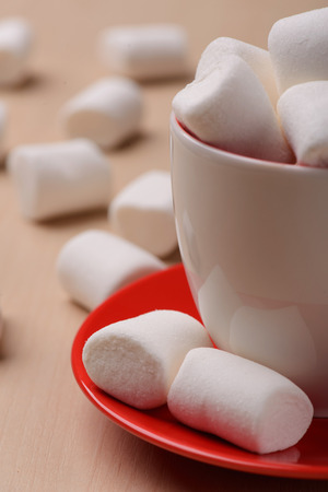 goodness: Enjoy some sugary sweet goodness. Closeup of the cup and plate full of white marshmallows