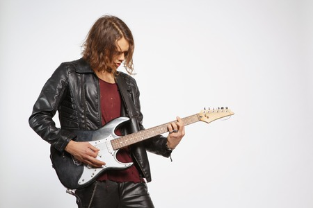 Creative soul. Handsome young man in leather jacket playing the guitar while standing on grey background