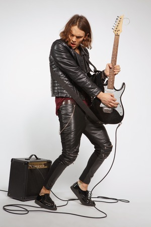 Singing his favorite song. Full-length portrait of handsome young man in leather jacket playing the guitar while standing on grey background