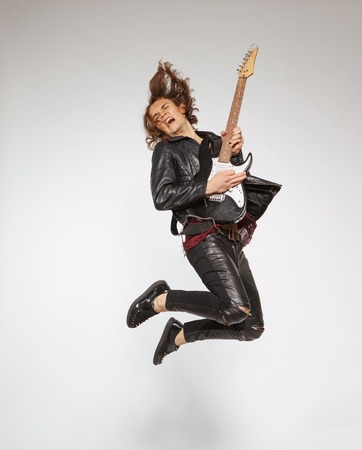 know how: For those who know how to rock. Full-length image of handsome young guitar player in leather suit jumping with the guitar and singing isolated on grey background