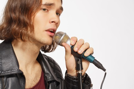 vocalist: Music from the heart. Closeup image of handsome young man in leather jacket singing in the microphone while standing on white background with copy space