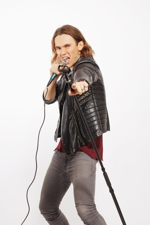 Singing  the blues away. Handsome young man in leather jacket singing in the microphone while standing isolated on white background with copy space