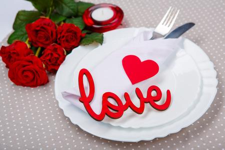 bougie coeur: Servir un peu de romantisme. Haut vue en gros plan de la romantique couverts d�ner avec le coeur rouge, bougie et amour lettrage sur la plaque blanche avec de belles roses � c�t� Banque d'images