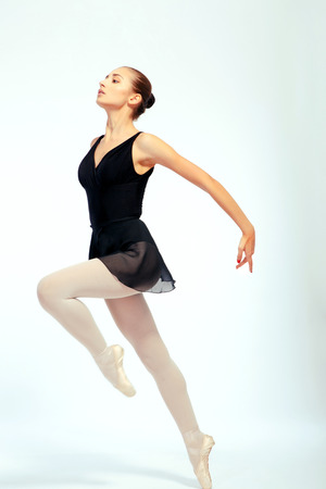 virtuoso: Ballet virtuoso. Full length portrait of beautiful ballet dancer in black ballet skirt taking a graceful jump isolated on white background