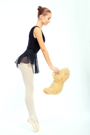tender tenderness: Tenderness. Side view  portrait of a beautiful tender ballet dancer in pointe holding a toy bear and looking down isolated on white background