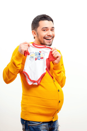 what if: What if men could bear children. Funny conceptual photo of gender reversal when a pregnant man with a belly holding a bodysuit and smiling while posing isolated on white background