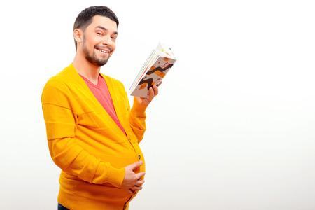 umschwung: Wachsende Erwartungen. Lustige konzeptuellen Foto von Gender Umkehr, wenn ein Mann mit einer schwangeren Bauch ein Buch zu lesen, w�hrend posiert auf wei�em Hintergrund Lizenzfreie Bilder